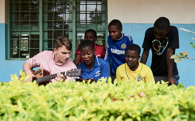 Young people sit together, one plays the guitar and the others sing.