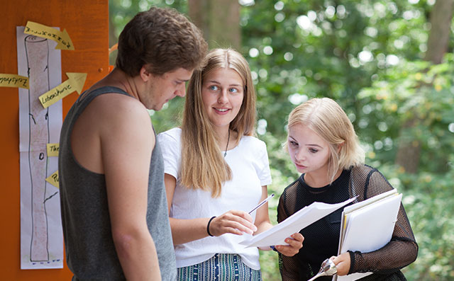 Three teenagers look at a piece of paper.