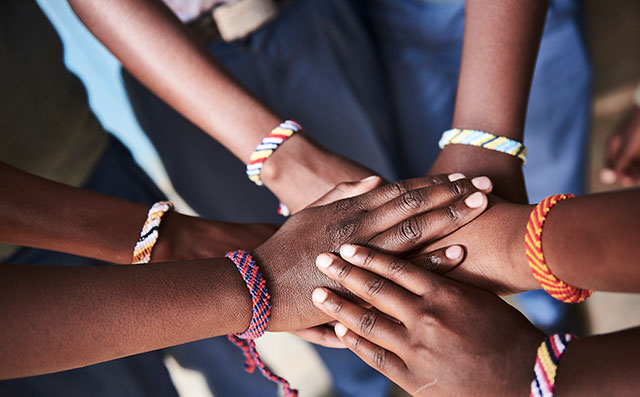 Several hands with colorful bracelets lie on top of each other.