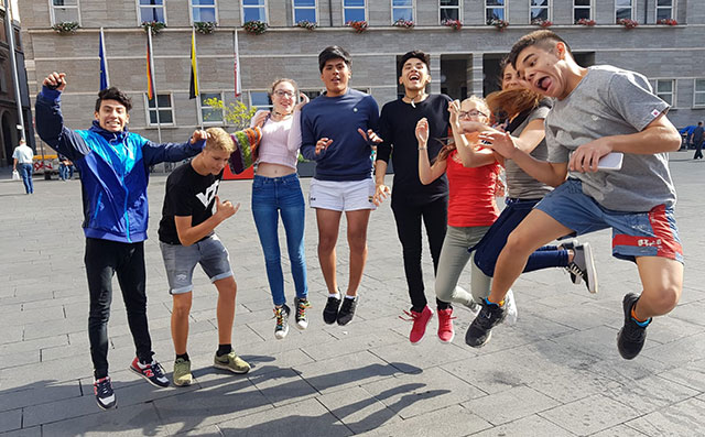 A group of young people jump in the air at the same time for a photo.